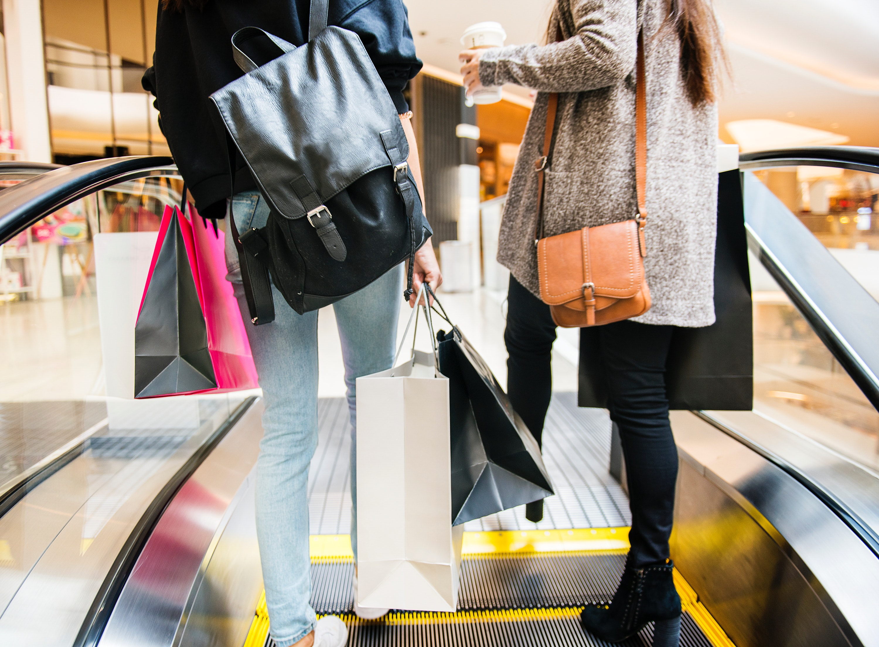 Two women holding shopping bags while riding an escalator.