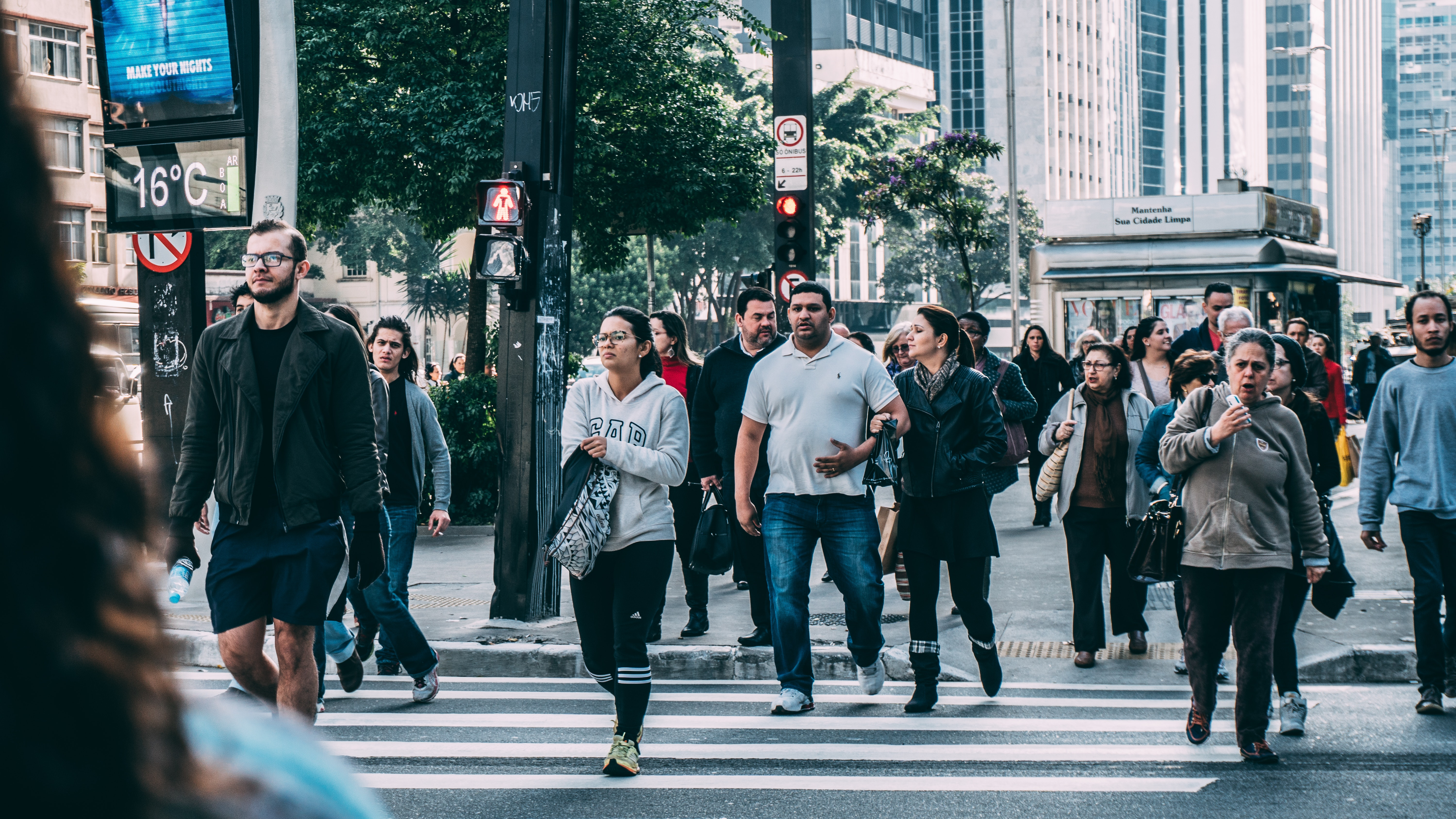 Crowd of people crossing a city crosswalk