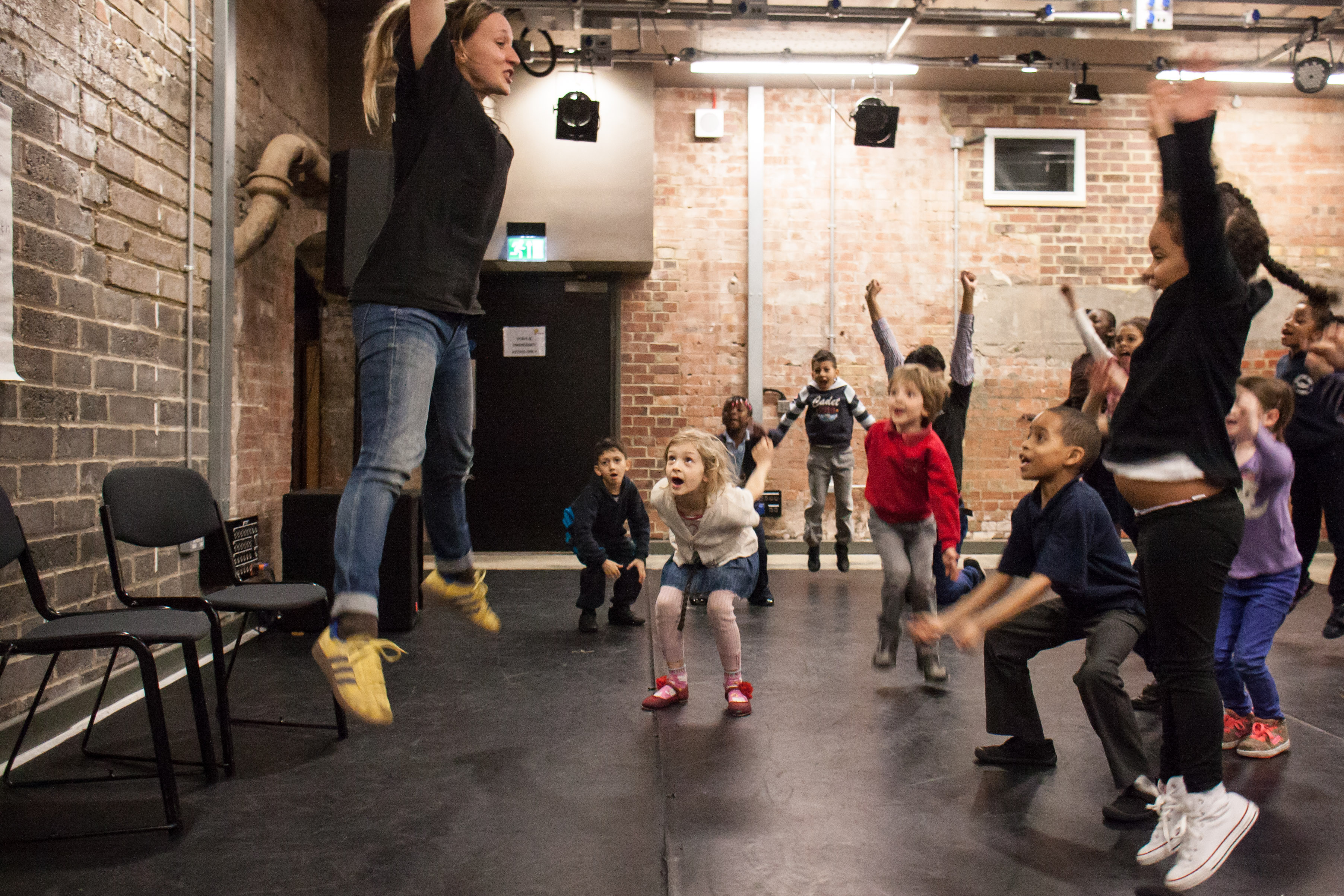 Woman at the front of the room jumping while children try to follow.