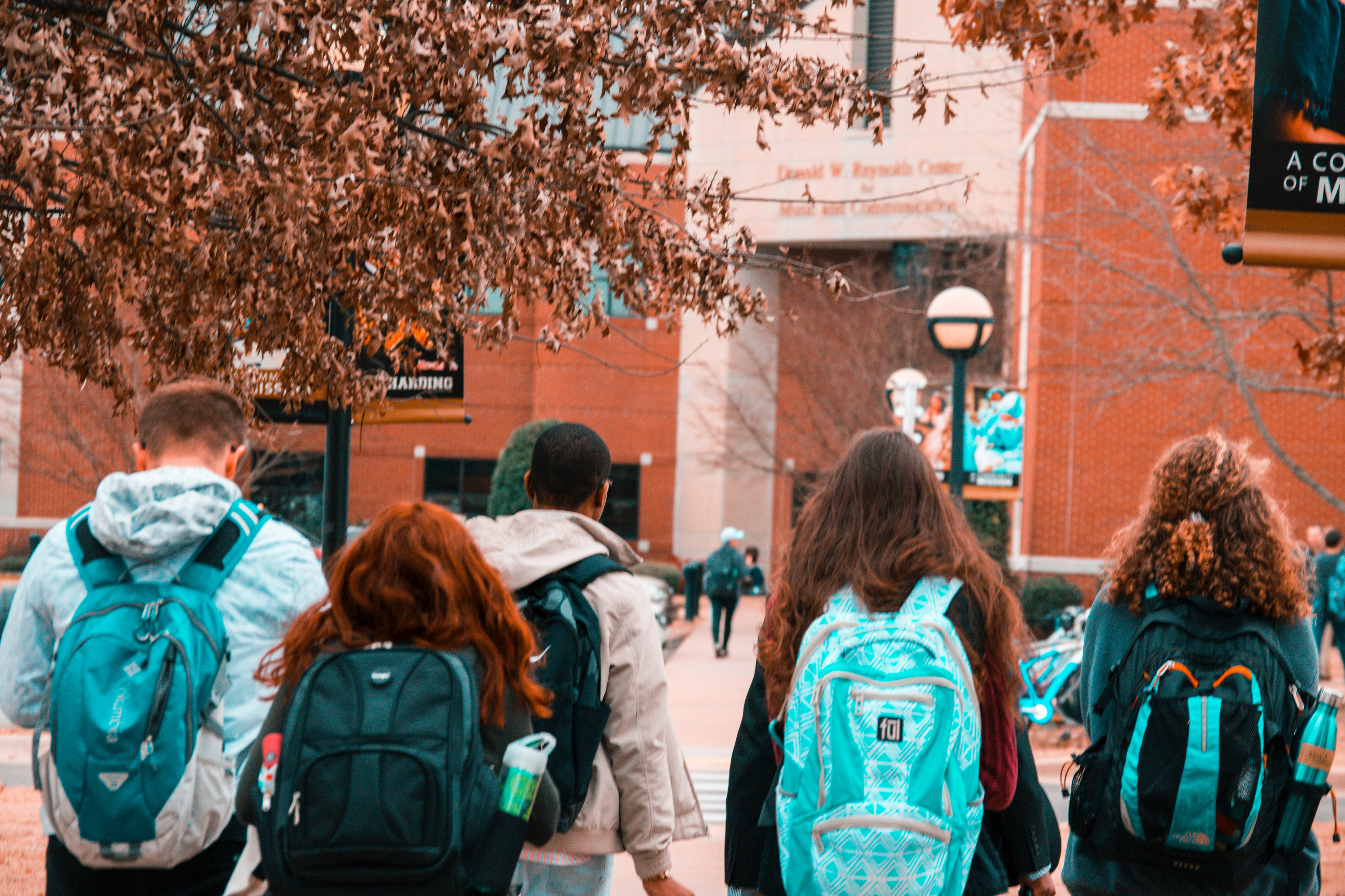 Students with backpacks walking into a brick building