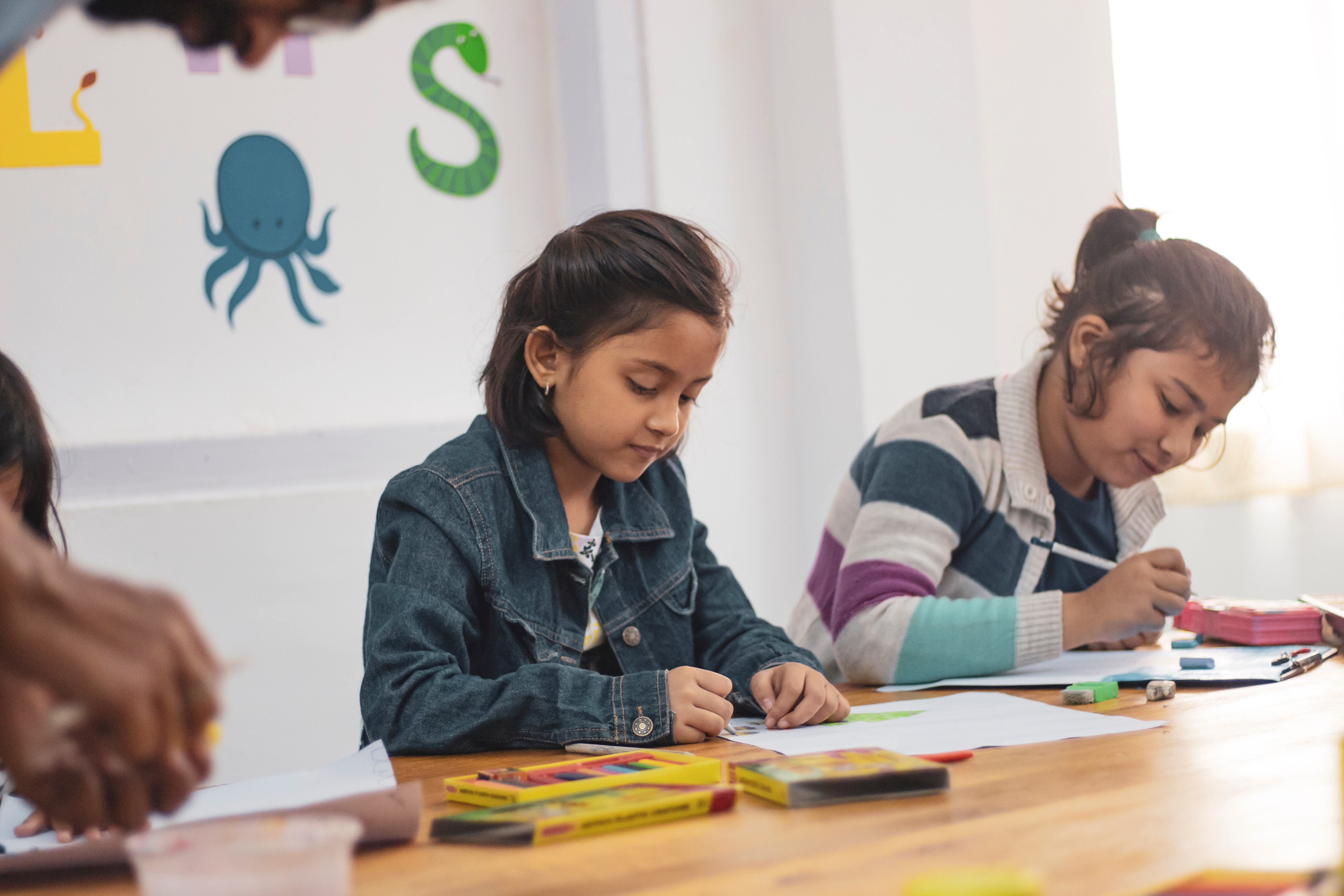 Two girls in school coloring at a table
