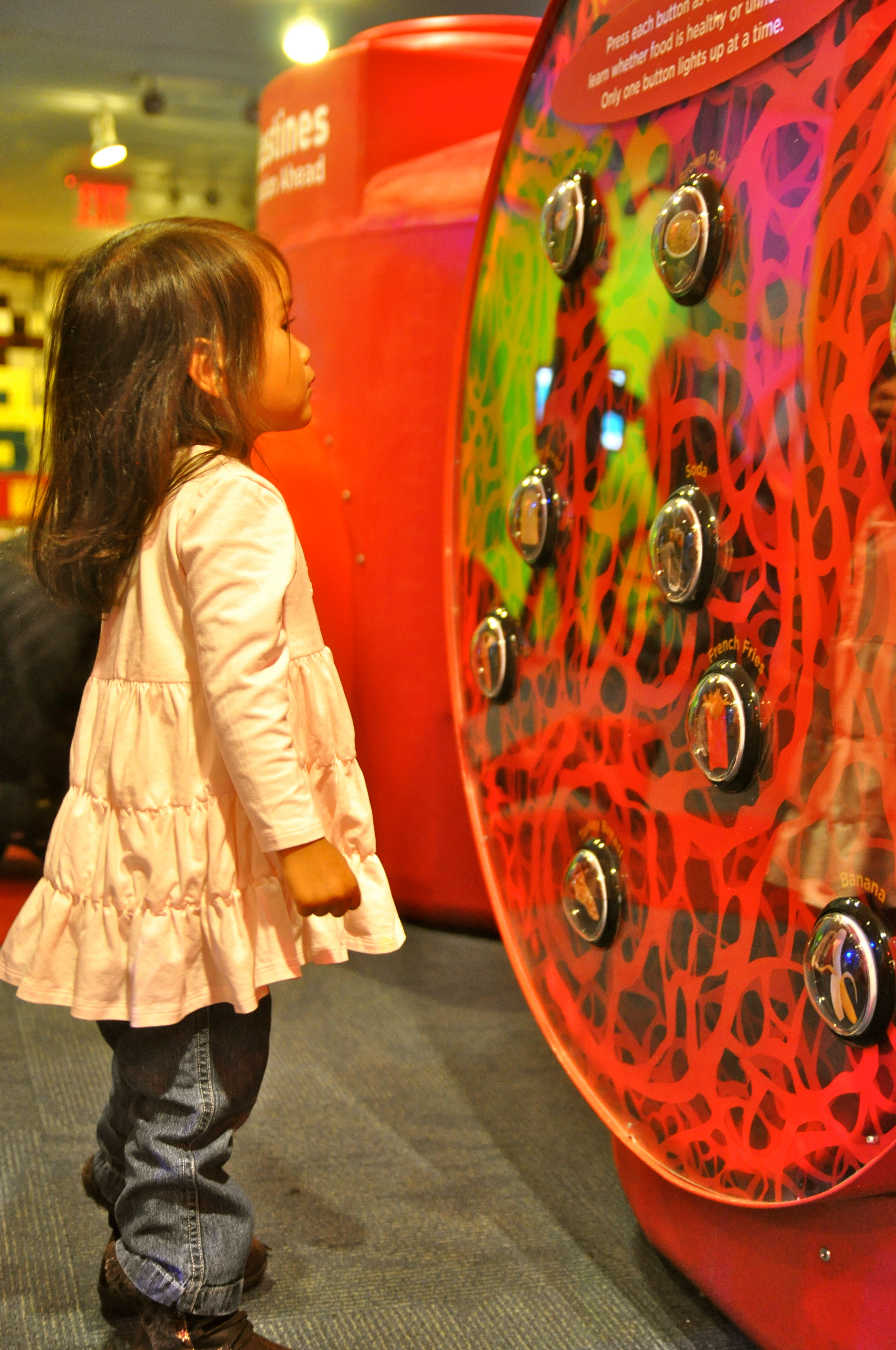 Young girl looking at red circle as a museum