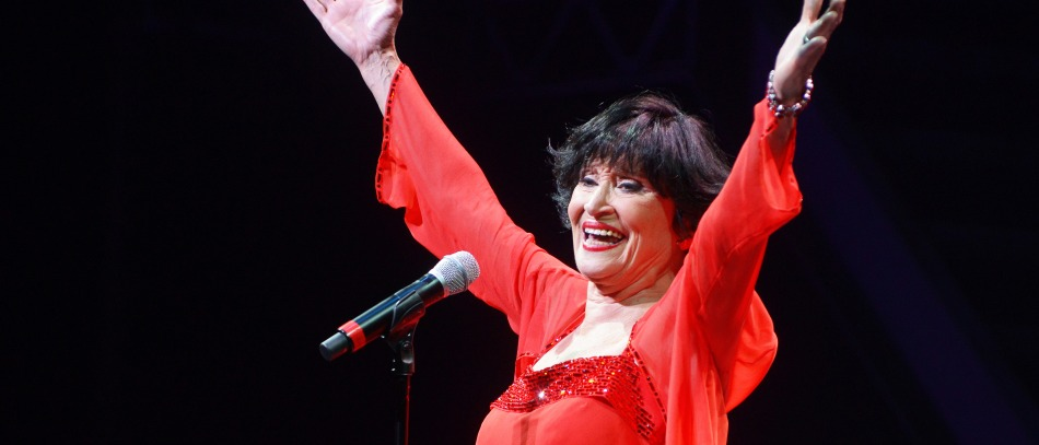 Chita Rivera performing on stage in a red dress