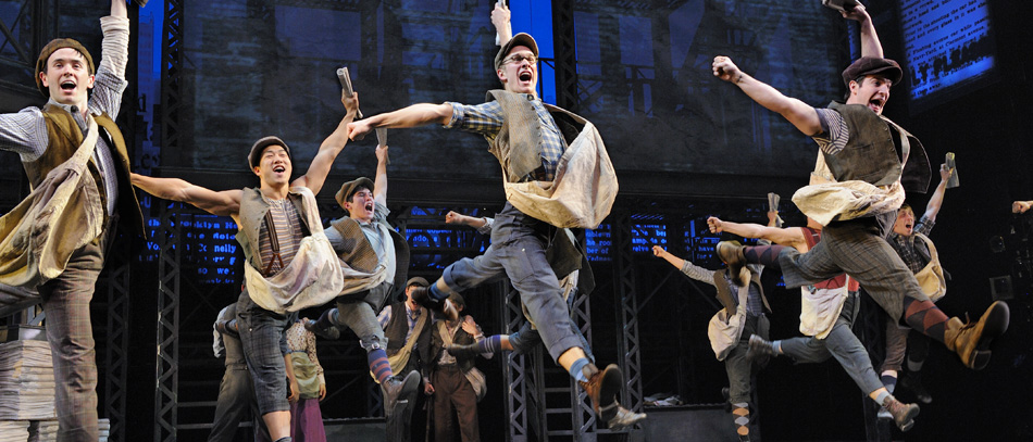 The Broadway cast of Disney's Newsies leaping through the air