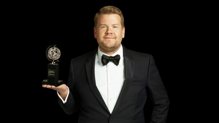 James Corden holding a Tony Award in a black Tuxedo for the Tony Awards