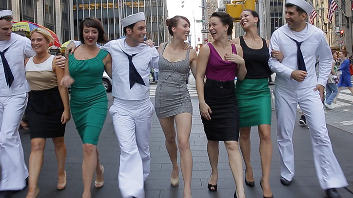 The Broadway cast of On The Town walking through Times Square