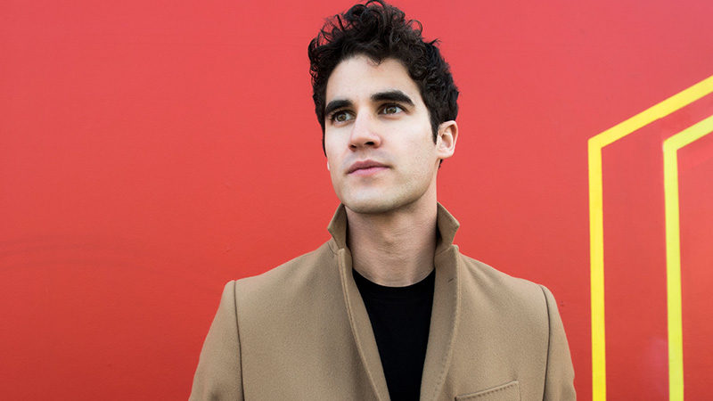Darren Criss standing in front of a red and yellow geometric background