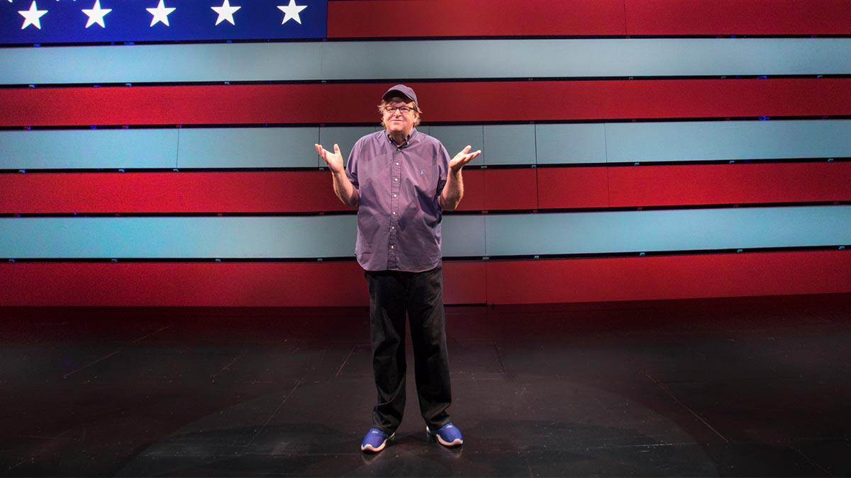 Michael Moore standing in front of the American flag