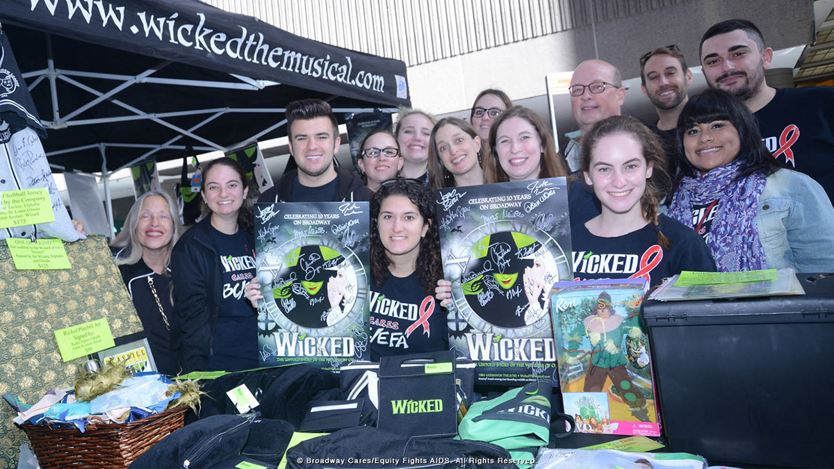 Fans of the Broadway musical Wicked holding up exclusive merchandise and surprises at the Broadway flea market