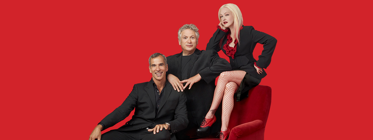 Jerry Mitchell, Harvey Fierstein, and Cyndi Lauper sitting on a chair in front of a bright red background.