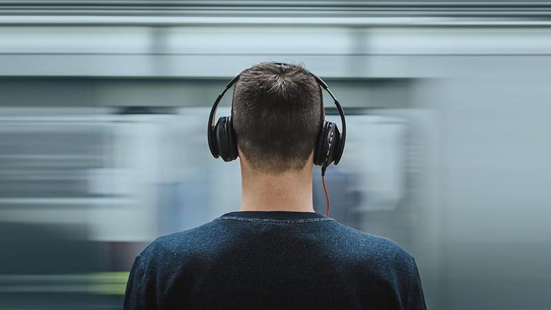 TGIF Tunes | a young man standing on a subway platform while listening to music through headphones