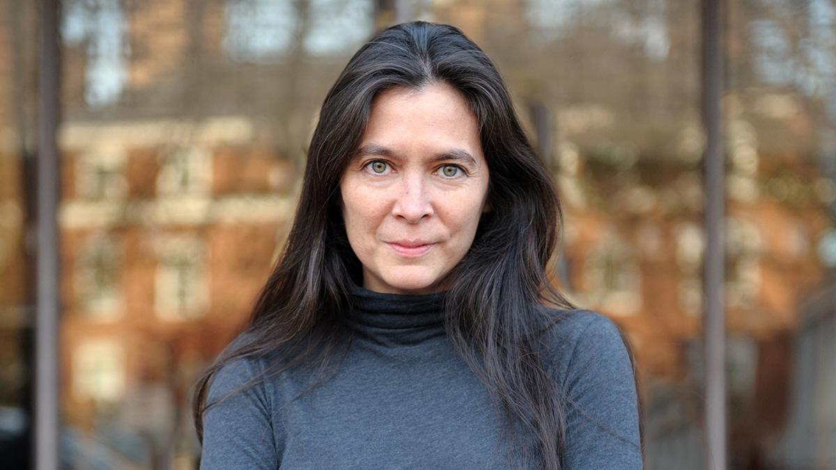 Diane Paulus wearing a gray turtleneck in front of a reflective surface in a metropolitan area.