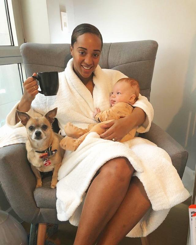 Sherisse Springer in a bath robe sitting on a chair with her dog, a cup of coffee, and her son Jackson.