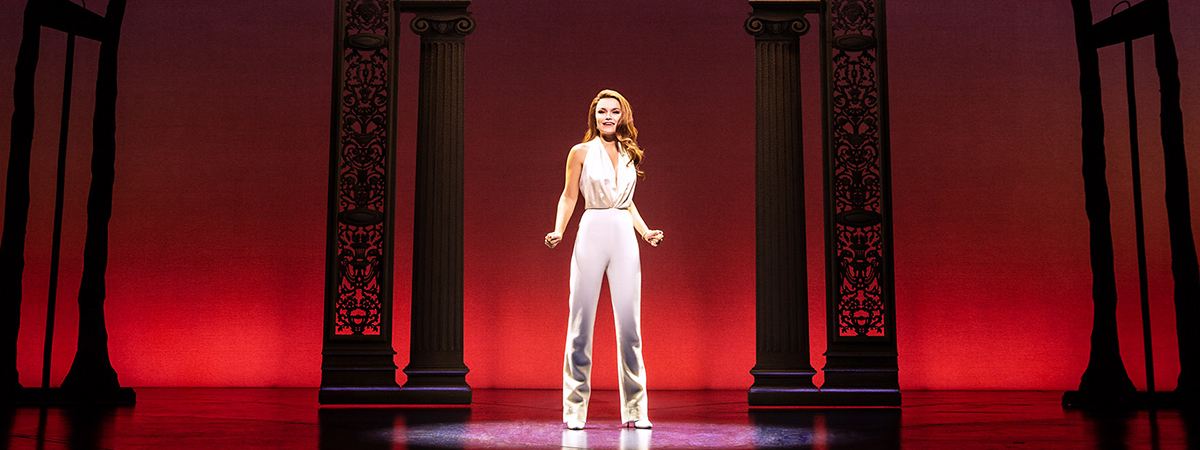 Samantha Barks in the Broadway production of Pretty Woman The Musical in white slacks and a white halter top, in front of a red background.